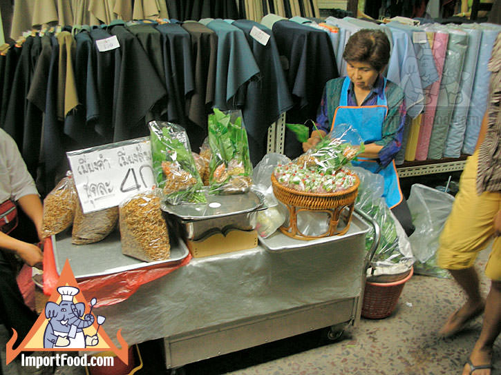 Bangkok Vendor Prepares Miang Kham on a Busy Pathway in the Fabric District