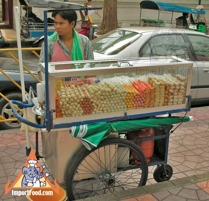 Thai Street Vendor Offers Assorted Deep-Fried Meatballs from a Push Cart