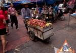 Pushing a Fruit Cart At Busy Thai Market