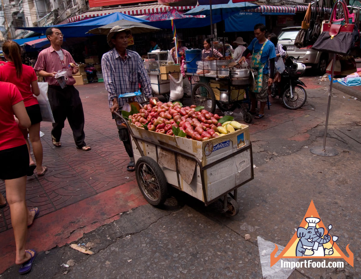 Pushing a Fruit Cart At Busy Thai Market