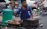 Thai Street Vendor with assorted skewers & sticky rice on a charcoal barbecue cart at a busy intersection.