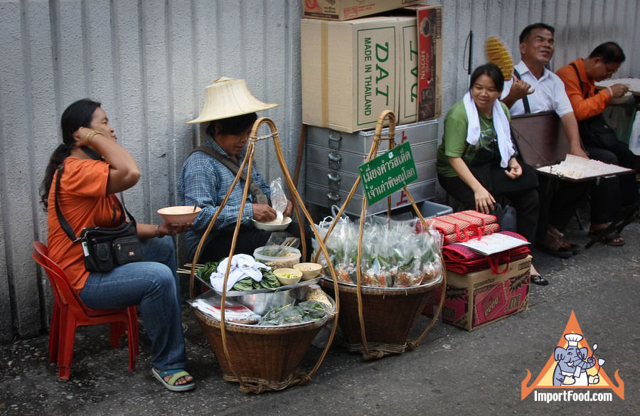Thai Street Vendor hand wrapping Miang Kahm